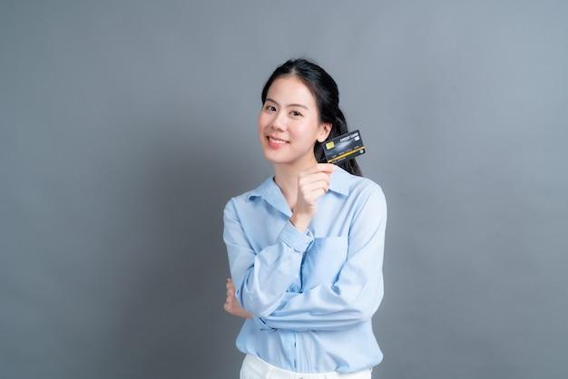 Portret van een mooie jonge aziatische vrouw in blauw shirt met creditcard met kopie ruimte op grijze muur