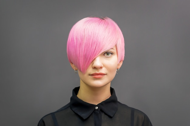Portret van een mooie jonge blanke vrouw met kort helder roze haar. professionele haarkleuring