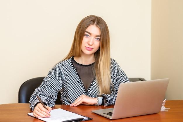 Portret van een mooie jonge blanke vrouw zittend aan de tafel werken met documenten in een kantoor