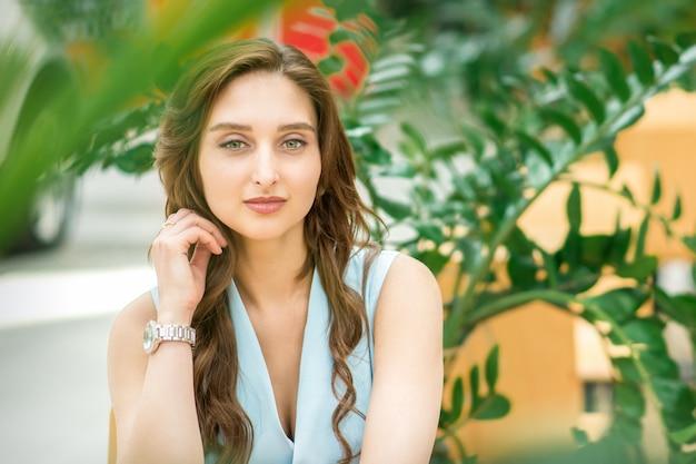 Portret van een mooie jonge blanke vrouwenzitting in bloementuin buitenshuis
