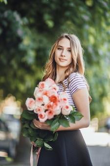 Portret van een mooie jonge blonde vrouw die staat met een bos rozen