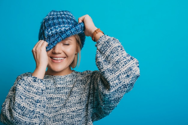 Portret van een mooie jonge blonde vrouw lachend met gesloten ogen terwijl ze haar gezicht verbergt met een blauwe hoed geïsoleerd op een blauwe achtergrond.