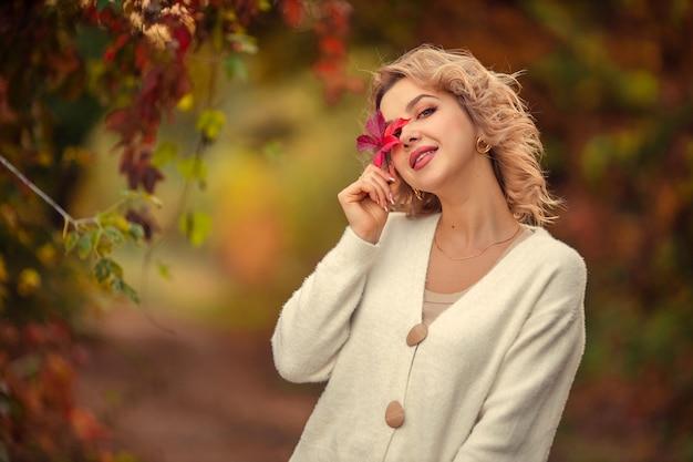 Portret van een mooie jonge blonde vrouw met een rood blad in haar handen in een herfst park.