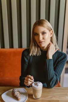 Portret van een mooie jonge blonde vrouw met koffie