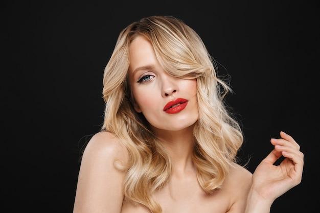 Portret van een mooie jonge blonde vrouw met lichte make-up rode lippen poseren geïsoleerd.