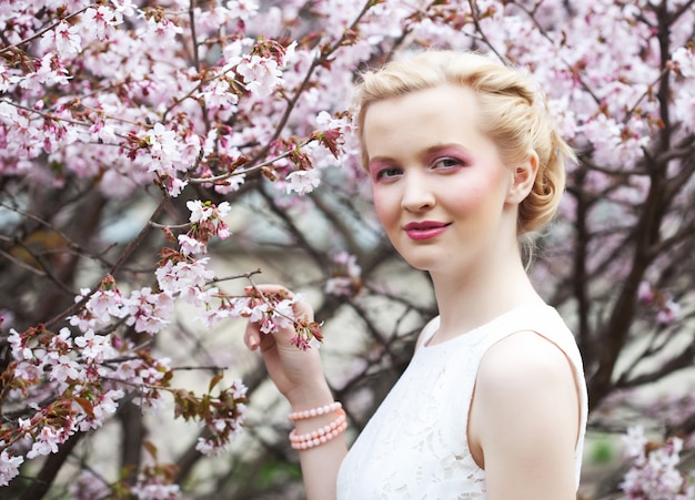 Portret van een mooie jonge blonde vrouw op een achtergrond van roze kersenbloesem in het voorjaar