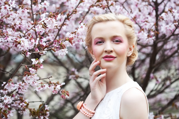 Portret van een mooie jonge blonde vrouw op een van roze kersenbloesems in het voorjaar