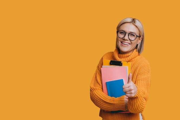Portret van een mooie jonge blonde vrouwelijke student die camera het glimlachen bekijkt terwijl het tonen van duim omhoog houdt die haar boek houdt dat op gele studiomuur wordt geïsoleerd.