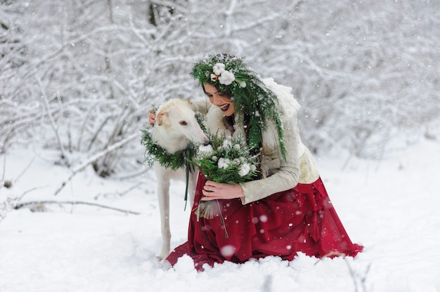 Portret van een mooie jonge bruid die speelt met een jachthond. winter huwelijksceremonie.