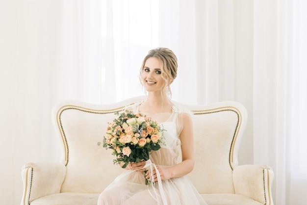 Portret van een mooie jonge bruid in een lichte kamer in een romantische sfeer. bruid in een negligé met een bruidsboeket