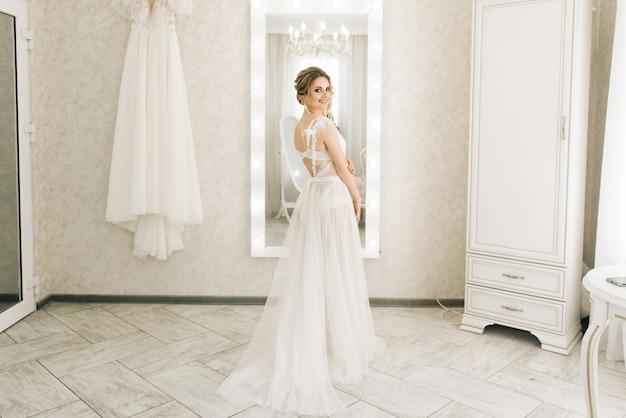 Portret van een mooie jonge bruid in een lichte kamer in een romantische sfeer. bruid in een negligé met huwelijkshaar en make-up