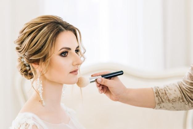Portret van een mooie jonge bruid in een lichte kamer in een romantische sfeer. bruiden doen make-up