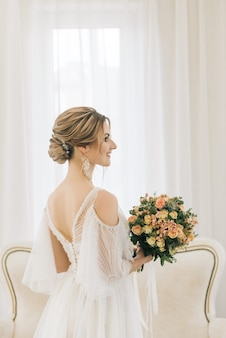 Portret van een mooie jonge bruid in een lichte kamer in een romantische sfeer. close-up van huwelijksmake-up en kapsel