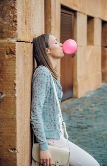 Portret van een mooie jonge brunette tienermeisje die roze kauwgom blaast en rust over een stenen muur