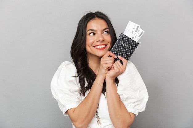 Portret van een mooie jonge brunette vrouw die een zomeroutfit draagt die geïsoleerd over een grijze muur staat en een paspoort met vliegtickets toont