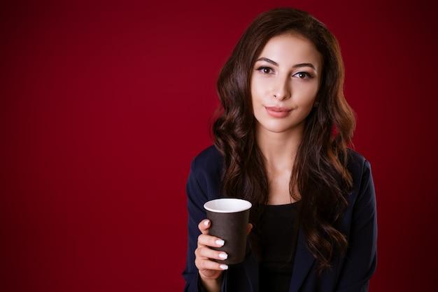 Portret van een mooie jonge brunette vrouw in een jasje met koffie in de hand