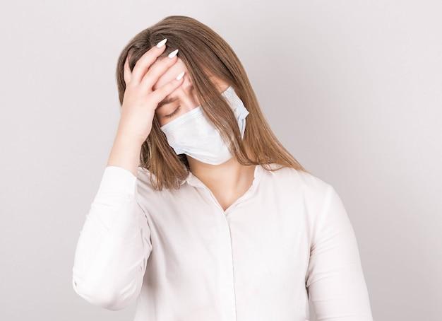 Portret van een mooie jonge brunette vrouw in een masker, in een witte blouse met slordig haar
