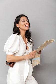 Portret van een mooie jonge brunette vrouw met een zomeroutfit die geïsoleerd staat over een grijze muur, kijkend naar de reiskaart