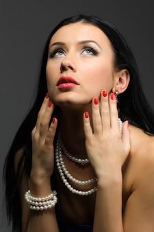 Portret van een mooie jonge brunette vrouw met mooie sieraden, make-up en manicure op een grijze achtergrond in de studio. advertentie ruimte