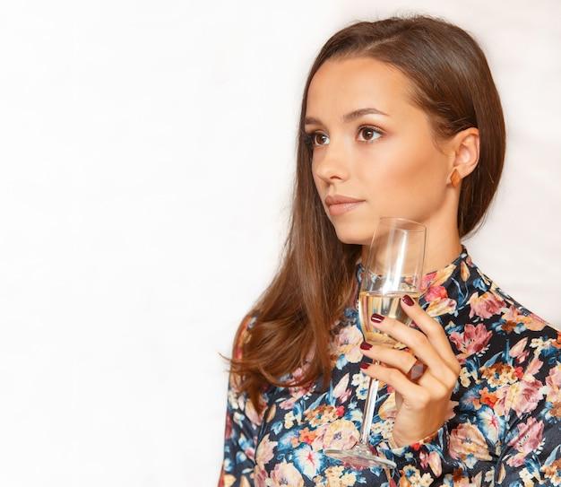 Portret van een mooie jonge brunette vrouw proeven, witte wijn controleren