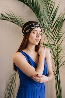 Portret van een mooie jonge brunnette vrouw met een plant