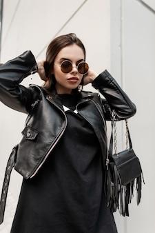 Portret van een mooie jonge coole vrouw met vintage ronde zonnebril in modieuze zwarte kleding: rock leren jas en sweatshirt met een stijlvolle handtas wandelingen in de stad. stedelijke vrouwelijke stijl