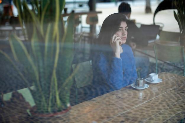 Portret van een mooie jonge dame gebruikend smartphone en bekijkend weg door glas terwijl het zitten bij lijst in een koffie