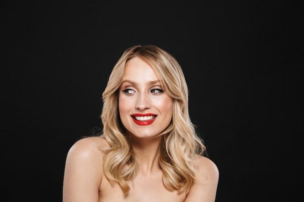 Portret van een mooie jonge gelukkige vrolijke blonde vrouw met heldere make-up rode lippen poseren geïsoleerd.