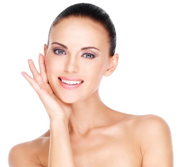 Portret van een mooie jonge glimlachende vrouw met gezonde frisse huid van het gezicht - geïsoleerd op wit