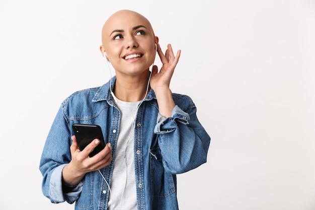 Portret van een mooie jonge haarloze vrouw die vrijetijdskleding draagt die geïsoleerd staat, naar muziek luistert met oortelefoons, mobiele telefoon vasthoudt