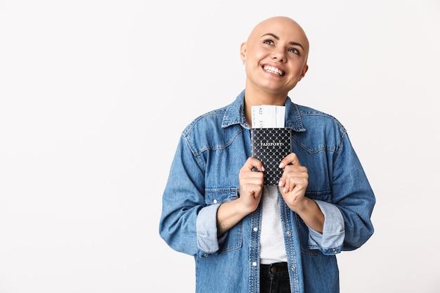Portret van een mooie jonge haarloze vrouw die vrijetijdskleding draagt die geïsoleerd staat, paspoort met vliegtickets toont