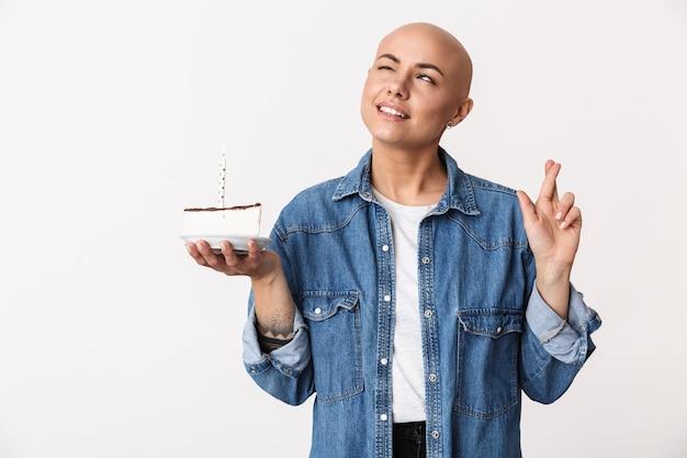 Portret van een mooie jonge haarloze vrouw met vrijetijdskleding die geïsoleerd staat en verjaardag viert met cake