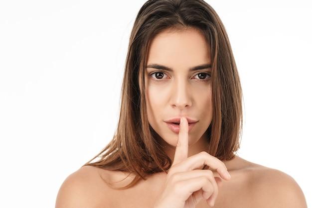 Portret van een mooie jonge, halfnaakte vrouw die naar de camera kijkt en een vinger op haar lippen houdt