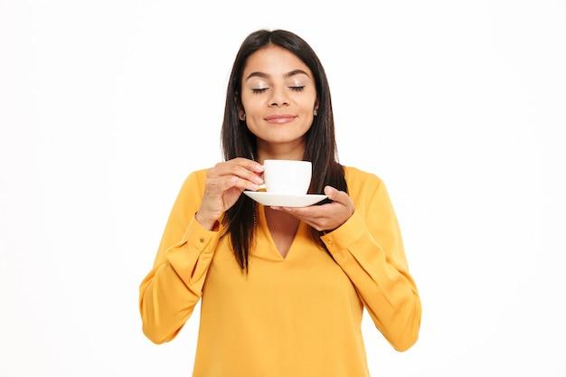 Portret van een mooie jonge kop van de vrouwen ruikende thee