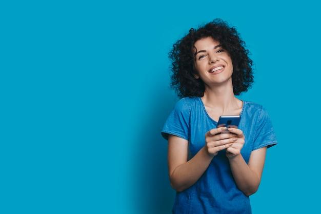Portret van een mooie jonge krullende vrouw gekleed in spijkerbroek jurk lachen terwijl kijken naar camera geïsoleerd op blauwe studio muur aanraken van haar gezicht.