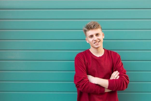 Portret van een mooie jonge man in een rode sweater, staat op turquoise muur