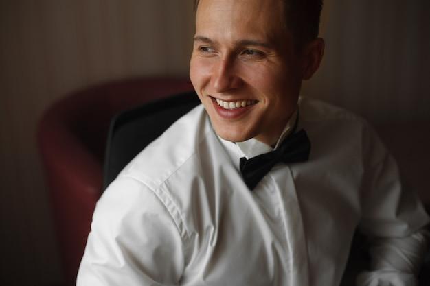 Portret van een mooie jonge man in een wit shirt met een zwarte vlinder