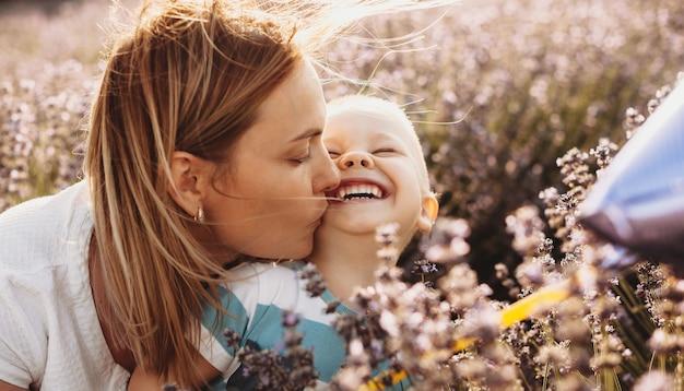 Portret van een mooie jonge moeder die haar klein kind kust terwijl hij met gesloten ogen bij de zonsondergang in een gebied van bloemen lacht.
