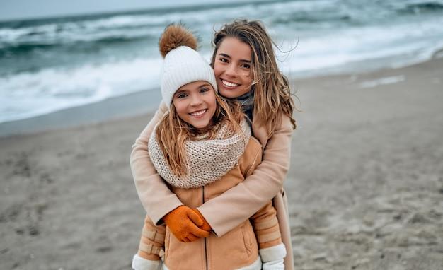 Portret van een mooie jonge moeder in een jas met haar schattige dochter in een gebreide muts op het strand in de winter.