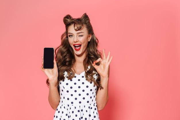 Portret van een mooie jonge pin-up girl gekleed in een jurk staande geïsoleerd, met lege scherm mobiele telefoon