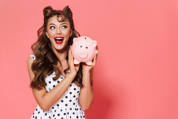 Portret van een mooie jonge pin-up girl gekleed in een jurk staande geïsoleerd, met spaarpot