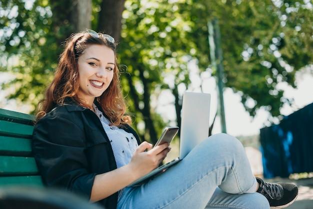 Portret van een mooie jonge positieve vrouw die direct lacht terwijl ze op een bankje zit met een laptop op de benen en een smartphone in de hand.