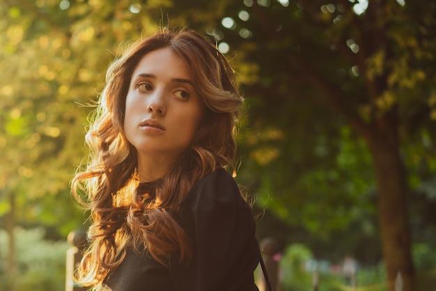 Portret van een mooie jonge trieste vrouw bij zonsondergang in de zon