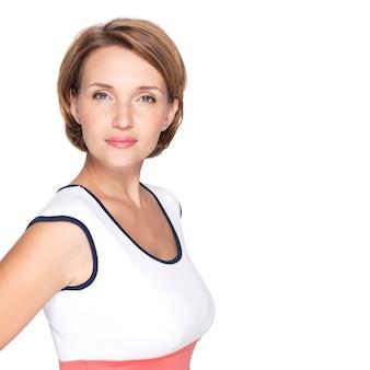 Portret van een mooie jonge volwassen witte ernstige vrouw over witte muur