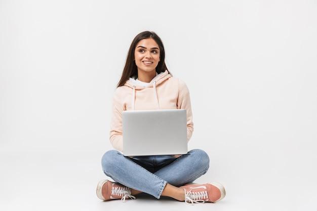 Portret van een mooie jonge vrouw casual gekleed zittend, benen gekruist geïsoleerd op wit, met behulp van laptop computer