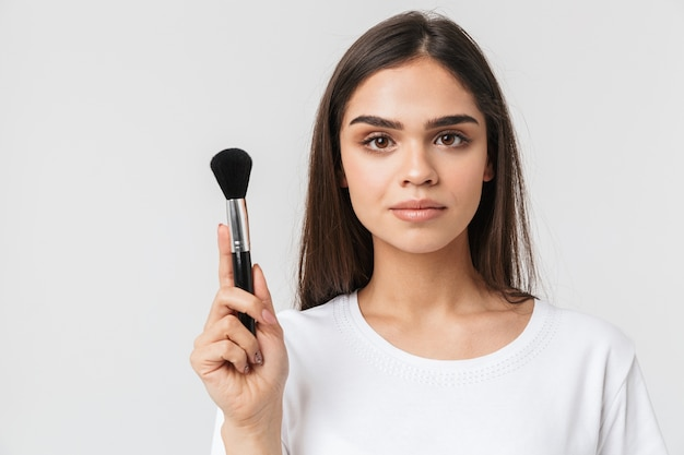 Portret van een mooie jonge vrouw casualy gekleed geïsoleerd op wit, make-up met een borstel toe te passen