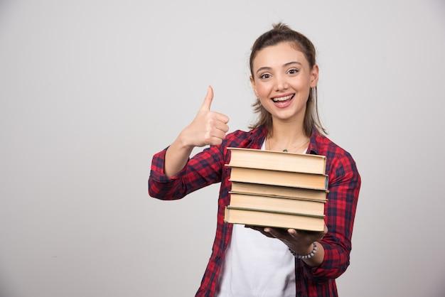 Portret van een mooie jonge vrouw die boeken vasthoudt en een duim toont.