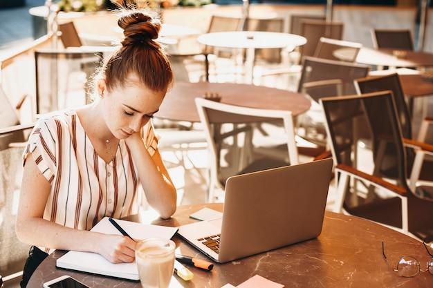 Portret van een mooie jonge vrouw die buiten aan haar boek werkt