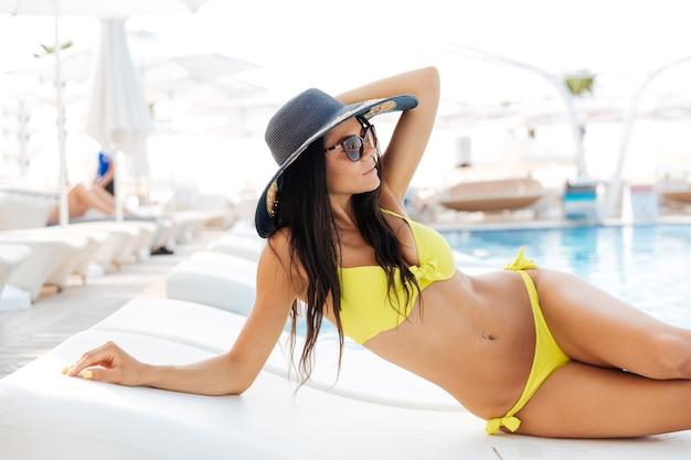 Portret van een mooie jonge vrouw die buiten op een ligstoel bij het zwembad ligt?