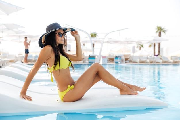 Portret van een mooie jonge vrouw die buiten op een ligstoel bij het zwembad zit